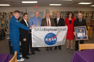 KENNEDY SPACE CENTER, FLA. - Center Director Jim Kennedy (center) and astronaut Roger Crouch (far left) present a NASA Explorer School (NES) banner to the NES team at South Plantation High School in Plantation, Fla. Kennedy, Crouch and other NASA KSC officials are visiting the school to share the vision for space exploration with the next generation. During the visit, Crouch is talking with students about our destiny as explorers, NASA's stepping stone approach to exploring Earth, the moon, Mars and beyond, how space impacts our lives, and how people and machines rely on each other in space. The Agency's NES program establishes a three-year partnership annually between NASA and 50 NASA Explorer School teams, consisting of teachers and education administrators from diverse communities nationwide. Photo credit: NASA/Cory Huston