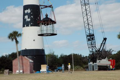 KENNEDY SPACE CENTER, FLA. - At Cape Canaveral Air Force Station, workers below help guide the detached lamp room from the Cape Canaveral Lighthouse onto the ground. Leaks in the roof allowed moisture to seep in. The lamp room is being removed for repairs and refurbishment. In addition, the original brass roof will be restored and put back in place. The Cape Canaveral Lighthouse is the only operational lighthouse owned by the Air Force. It was first erected in 1868 near the edge of the Atlantic Ocean. Photo credit: NASA/Jack Pfaller