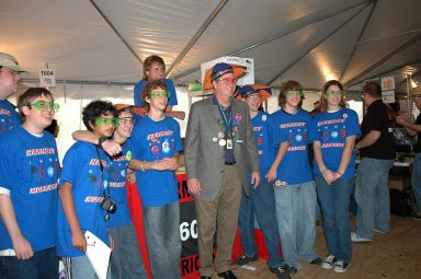 """KENNEDY SPACE CENTER, FLA. - During the 2006 FIRST Robotics Regional Competition held March 9-11 at the University of Central Florida in Orlando, Florida Governor Jeb Bush poses with the student team from Harmony High School in Florida called The Harmony Hurricanes. The high school was teamed with DeVry University, Disney World and the Town of Harmony. The FIRST Robotics Competition challenges teams of young people and their mentors to solve a common problem in a six-week timeframe using a standard """"kit of parts"""" and a common set of rules. Teams build robots from the parts and enter them in a series of competitions. FIRST, which is based on """"For Inspiration and Recognition of Science and Technology,"""" redefines winning for these students. Teams are rewarded for excellence in design, demonstrated team spirit, gracious professionalism and maturity, and ability to overcome obstacles. Scoring the most points is a secondary goal. Winning means building partnerships that last. NASA and the University of Central Florida are co-sponsors of the regional event, which this year included more than 50 teams. Photo credit: NASA/Kim Shiflett"""