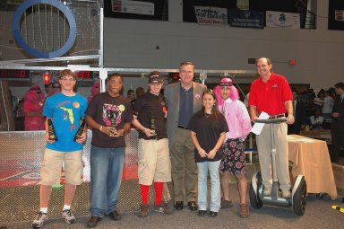 """KENNEDY SPACE CENTER, FLA. - During opening ceremonies of the 2006 FIRST Robotics Regional Competition held March 9-11 at the University of Central Florida in Orlando, Florida Governor Jeb Bush poses with recipients of the Governor's Award trophy. The FIRST Robotics Competition challenges teams of young people and their mentors to solve a common problem in a six-week timeframe using a standard """"kit of parts"""" and a common set of rules. Teams build robots from the parts and enter them in a series of competitions. FIRST, which is based on """"For Inspiration and Recognition of Science and Technology,"""" redefines winning for these students. Teams are rewarded for excellence in design, demonstrated team spirit, gracious professionalism and maturity, and ability to overcome obstacles. Scoring the most points is a secondary goal. Winning means building partnerships that last. NASA and the University of Central Florida are co-sponsors of the regional event, which this year included more than 50 teams. Photo credit: NASA/Kim Shiflett"""