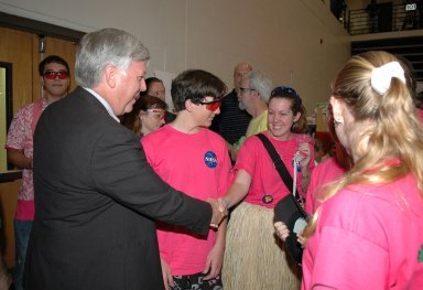 """KENNEDY SPACE CENTER, FLA. - During the 2006 FIRST Robotics Regional Competition held March 9-11 at the University of Central Florida in Orlando, Kennedy Space Center Director Jim Kennedy (left) greets members of the """"Pink Team,"""" whose robot is named Roccobot and is co-sponsored by NASA KSC. At least four teams in the competition were sponsored by KSC, NASA and contractors. The FIRST Robotics Competition challenges teams of young people and their mentors to solve a common problem in a six-week timeframe using a standard """"kit of parts"""" and a common set of rules. Teams build robots from the parts and enter them in a series of competitions. FIRST, which is based on """"For Inspiration and Recognition of Science and Technology,"""" redefines winning for these students. Teams are rewarded for excellence in design, demonstrated team spirit, gracious professionalism and maturity, and ability to overcome obstacles. Scoring the most points is a secondary goal. Winning means building partnerships that last. NASA and the University of Central Florida are co-sponsors of the regional event, which this year included more than 50 teams. Photo credit: NASA/Kim Shiflett"""