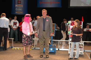 """KENNEDY SPACE CENTER, FLA. - Opening ceremonies of the 2006 FIRST Robotics Regional Competition held March 9-11 at the University of Central Florida in Orlando included Florida Governor Jeb Bush (center). At left is Sam Mallikarjunan from Rockledge High School, and at right is Stephanie Alphonso from Freedom High School in Orlando. The FIRST Robotics Competition challenges teams of young people and their mentors to solve a common problem in a six-week timeframe using a standard """"kit of parts"""" and a common set of rules. Teams build robots from the parts and enter them in a series of competitions. FIRST, which is based on """"For Inspiration and Recognition of Science and Technology,"""" redefines winning for these students. Teams are rewarded for excellence in design, demonstrated team spirit, gracious professionalism and maturity, and ability to overcome obstacles. Scoring the most points is a secondary goal. Winning means building partnerships that last. NASA and the University of Central Florida are co-sponsors of the regional event, which this year included more than 50 teams. Photo credit: NASA/Kim Shiflett"""