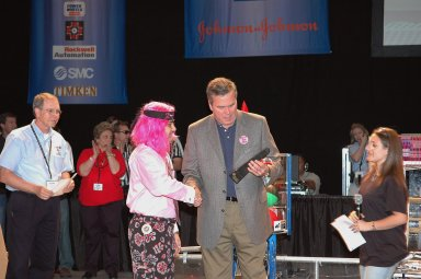 """KENNEDY SPACE CENTER, FLA. - During opening ceremonies of the 2006 FIRST Robotics Regional Competition held March 9-11 at the University of Central Florida in Orlando, Florida Governor Jeb Bush receives the inaugural Governor's Award trophy from Sam Mallikarjunan from Rockledge High School and Stephanie Alphonso from Freedom High School in Orlando. The FIRST Robotics Competition challenges teams of young people and their mentors to solve a common problem in a six-week timeframe using a standard """"kit of parts"""" and a common set of rules. Teams build robots from the parts and enter them in a series of competitions. FIRST, which is based on """"For Inspiration and Recognition of Science and Technology,"""" redefines winning for these students. Teams are rewarded for excellence in design, demonstrated team spirit, gracious professionalism and maturity, and ability to overcome obstacles. Scoring the most points is a secondary goal. Winning means building partnerships that last. NASA and the University of Central Florida are co-sponsors of the regional event, which this year included more than 50 teams. Photo credit: NASA/Kim Shiflett"""