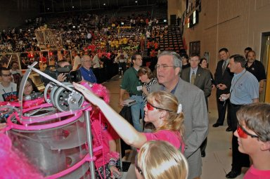 """KENNEDY SPACE CENTER, FLA. - Members of the """"Pink Team"""" explain their robot to Florida Governor Jeb Bush at the 2006 FIRST Robotics Regional Competition held March 9-11 at the University of Central Florida in Orlando. The Pink Team, whose robot is named Roccobot, is co-sponsored by NASA KSC. At least four teams in the competition were sponsored by KSC, NASA and contractors. The FIRST Robotics Competition challenges teams of young people and their mentors to solve a common problem in a six-week timeframe using a standard """"kit of parts"""" and a common set of rules. Teams build robots from the parts and enter them in a series of competitions. FIRST, which is based on """"For Inspiration and Recognition of Science and Technology,"""" redefines winning for these students. Teams are rewarded for excellence in design, demonstrated team spirit, gracious professionalism and maturity, and ability to overcome obstacles. Scoring the most points is a secondary goal. Winning means building partnerships that last. NASA and the University of Central Florida are co-sponsors of the regional event, which this year included more than 50 teams. Photo credit: NASA/Kim Shiflett"""