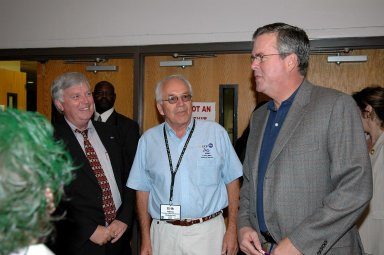 """KENNEDY SPACE CENTER, FLA. - During the 2006 FIRST Robotics Regional Competition held March 9-11 at the University of Central Florida in Orlando, Kennedy Space Center Director Jim Kennedy (left) and Florida Governor Jeb Bush (right) are joined by Erik Halleus, executive chair of the Florida FIRST committee.The FIRST Robotics Competition challenges teams of young people and their mentors to solve a common problem in a six-week timeframe using a standard """"kit of parts"""" and a common set of rules. Teams build robots from the parts and enter them in a series of competitions. FIRST, which is based on """"For Inspiration and Recognition of Science and Technology,"""" redefines winning for these students. Teams are rewarded for excellence in design, demonstrated team spirit, gracious professionalism and maturity, and ability to overcome obstacles. Scoring the most points is a secondary goal. Winning means building partnerships that last. NASA and the University of Central Florida are co-sponsors of the regional event, which this year included more than 50 teams. Photo credit: NASA/Kim Shiflett"""