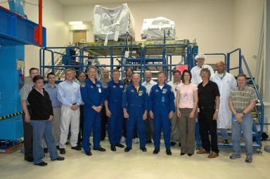 KENNEDY SPACE CENTER, FLA. - Members of the STS-121 crew pose with workers in the SPACEHAB facility in Cape Canaveral during the Crew Equipment Interface Test. The astronauts (in blue suits) are Mission Specialists Piers Sellers and Michael Fossum, Pilot Mark Kelly and Commander Steven Lindsey. This test allows the astronauts to become familiar with equipment they will be using on their upcoming mission. STS-121 is scheduled to launch in July aboard Space Shuttle Discovery. Photo credit: NASA/Kim Shiflett
