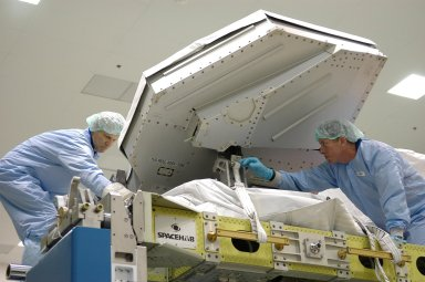 KENNEDY SPACE CENTER, FLA. - STS-121 Mission Specialist Piers Sellers (left) and Commander Steven Lindsey (right) are practicing removing the cover and strap on the trailing umbilical assembly at the SPACEHAB facility in Cape Canaveral during a Crew Equipment Interface Test. This test allows the astronauts to become familiar with equipment they will be using on their upcoming mission. STS-121 is scheduled to launch in July aboard Space Shuttle Discovery. Photo credit: NASA/Kim Shiflett