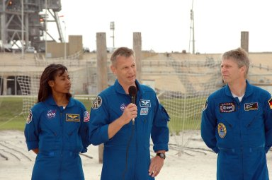 KENNEDY SPACE CENTER, FLA. - During a pause in their prelaunch activities at the pad, the STS-121 crew talk to the media. They are standing in the landing area of the slidewire baskets. With the microphone is Mission Specialist Piers Sellers. Next to him are Mission Specialists Stephanie Wilson and Thomas Reiter of Germany, who represents the European Space Agency. The crew is at Kennedy for Terminal Countdown Demonstration Test activities. Over several days, the crew will practice emergency egress from the pad and suit up in their orange flight suits for the simulated countdown to launch. Space Shuttle Discovery is designated to launch July 1 on mission STS-121. It will carry supplies to the International Space Station. Photo credit: NASA/Kim Shiflett