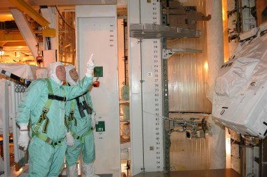 """KENNEDY SPACE CENTER, FLA. - Inside the payload changeout room on Launch Pad 39B, STS-121 Mission Specialists Michael Fossum (left) and Piers Sellers check out part of the payload for the mission. They are dressed in clean room suits, appropriate for the environmentally clean or """"white room"""" condition in which the payload resides before being transferred to the shuttle's payload bay. The payload includes the multi-purpose logistics module Leonardo, with supplies and equipment for the International Space Station; the lightweight multi-purpose experiment support structure carrier; and the integrated cargo carrier. Crew members are at NASA's Kennedy Space Center for Terminal Countdown Demonstration Test activities, which include equipment familiarization and a simulated launch countdown. Mission STS-121 is scheduled for launch on Space Shuttle Discovery on July 1. Photo credit: NASA/Kim Shiflett"""