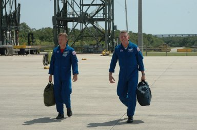KENNEDY SPACE CENTER, FLA. - After a three-day series of Terminal Countdown Demonstration Test (TCDT) activities, the crew of mission STS-121 are leaving NASA's Kennedy Space Center to return to Houston. Walking to the plane at the Shuttle Landing Facility are Commander Steven Lindsey (left) and Mission Specialist Michael Fossum. The TCDT includes equipment familiarization, emergency egress training and a simulated launch countdown. Mission STS-121 is scheduled to launch July 1. Photo credit: NASA/Kim Shiflett