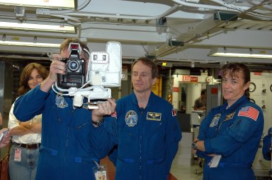 KENNEDY SPACE CENTER, FLA. - In the Orbiter Processing Facility, STS-115 Mission Specialist Joseph Tanner practices using a camera that is a mockup of one the crew will use to take photographs on-orbit. With him are Mission Specialists Steven MacLean, who represents the Canadian Space Agency, and Heidemarie Stefanyshyn-Piper. The crew is at the center for Crew Equipment Interface Test activities, which involves equipment familiarization, a routine part of astronaut training and launch preparations. The mission will deliver the second port truss segment, the P3/P4 Truss, to attach to the first port truss segment, the P1 Truss, as well as deploy solar array set 2A and 4A. Launch on Space Shuttle Atlantis is scheduled for late August. Photo credit: NASA/Kim Shiflett