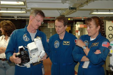KENNEDY SPACE CENTER, FLA. - In the Orbiter Processing Facility, STS-115 Mission Specialist Joseph Tanner gets familiar with a camera that is a mockup of one the crew will use to take photographs on-orbit. With him are Mission Specialists Steven MacLean, who represents the Canadian Space Agency, and Heidemarie Stefanyshyn-Piper. The crew is at the center for Crew Equipment Interface Test activities, which involves equipment familiarization, a routine part of astronaut training and launch preparations. The mission will deliver the second port truss segment, the P3/P4 Truss, to attach to the first port truss segment, the P1 Truss, as well as deploy solar array set 2A and 4A. Launch on Space Shuttle Atlantis is scheduled for late August. Photo credit: NASA/Kim Shiflett