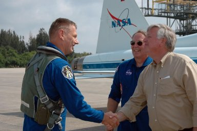 KENNEDY SPACE CENTER, FLA. - After his arrival at KSC, STS-121 Mission Specialist Piers Sellers is greeted by Center Director Jim Kennedy. Behind Kennedy is Jerry Ross, who is chief of the Vehicle Integration Test Office at Johnson Space Center. During the 12-day mission, the STS-121 crew will test new equipment and procedures to improve shuttle safety, as well as deliver supplies and make repairs to the International Space Station. This mission is the 115th shuttle flight and the 18th U.S. flight to the International Space Station. Photo credit: NASA/Kim Shiflett