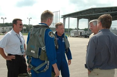 KENNEDY SPACE CENTER, FLA. - After their arrival at the Shuttle Landing Facility to get ready for launch July 1, STS-121 Mission Specialist Thomas Reiter (second from left) and Commander Steven Lindsey are greeted (at right) by Center Director Jim Kennedy and Shuttle Launch Director Mike Leinbach. During the 12-day mission, the STS-121 crew will test new equipment and procedures to improve shuttle safety, as well as deliver supplies and make repairs to the International Space Station. This mission is the 115th shuttle flight and the 18th U.S. flight to the International Space Station. Photo credit: NASA/Kim Shiflett