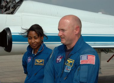 KENNEDY SPACE CENTER, FLA. - STS-121 Mission Specialist Stephanie Wilson and Pilot Mark Kelly walk across the Shuttle Landing Facility after their arrival to get ready for launch on July 1. The launch will be Wilson's first space flight. During the 12-day mission, the STS-121 crew will test new equipment and procedures to improve shuttle safety, as well as deliver supplies and make repairs to the International Space Station. This mission is the 115th shuttle flight and the 18th U.S. flight to the International Space Station. Photo credit: NASA/Kim Shiflett