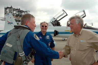 KENNEDY SPACE CENTER, FLA. - STS-121 Mission Specialist Michael Fossum (left) is greeted by Center Director Jim Kennedy after arriving at KSC to get ready for launch on July 1. Behind him is Jerry Ross, who is chief of the Vehicle Integration Test Office at Johnson Space Center. During the 12-day mission, the STS-121 crew will test new equipment and procedures to improve shuttle safety, as well as deliver supplies and make repairs to the International Space Station. This mission is the 115th shuttle flight and the 18th U.S. flight to the International Space Station. Photo credit: NASA/Kim Shiflett