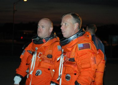 KENNEDY SPACE CENTER, FLA. - In the pre-dawn hours, STS-121 Pilot Mark Kelly (left) and Commander Steven Lindsey look at the Shuttle Training Aircraft (STA) they will be flying to practice landings in preparation for the July 1 launch of Space Shuttle Discovery. The STA is a Grumman American Aviation-built Gulf Stream II jet that was modified to simulate an orbiter?s cockpit, motion and visual cues, and handling qualities. In flight, the STA duplicates the orbiter?s atmospheric descent trajectory from approximately 35,000 feet altitude to landing on a runway. Because the orbiter is unpowered during re-entry and landing, its high-speed glide must be perfectly executed the first time. Photo credit: NASA/Kim Shiflett
