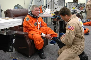 KENNEDY SPACE CENTER, FLA. - STS-121 Mission Specialist Michael Fossum is helped with his boot during suitup for launch today on Space Shuttle Discovery. The launch is the 115th shuttle flight and the 18th U.S. flight to the International Space Station. During the 12-day mission, the STS-121 crew will test new equipment and procedures to improve shuttle safety, as well as deliver supplies and make repairs to the International Space Station. Photo credit: NASA/Kim Shiflett