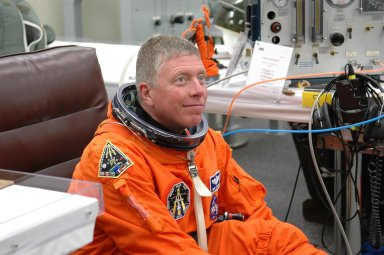 KENNEDY SPACE CENTER, FLA. - The STS-121 crew are donning their orange launch and entry suits for launch today on Space Shuttle Discovery. Seated here is Mission Specialist Michael Fossum, who is making his first space flight. The launch is the 115th shuttle flight and the 18th U.S. flight to the International Space Station. During the 12-day mission, the STS-121 crew will test new equipment and procedures to improve shuttle safety, as well as deliver supplies and make repairs to the International Space Station. Photo credit: NASA/Kim Shiflett