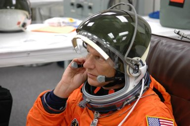 KENNEDY SPACE CENTER, FLA. - The STS-121 crew are donning their orange launch and entry suits for launch today on Space Shuttle Discovery. Here, Mission Specialist Piers Sellers adjusts part of his helmet. Sellers is making his second space flight. The launch is the 115th shuttle flight and the 18th U.S. flight to the International Space Station. During the 12-day mission, the STS-121 crew will test new equipment and procedures to improve shuttle safety, as well as deliver supplies and make repairs to the International Space Station. Photo credit: NASA/Kim Shiflett