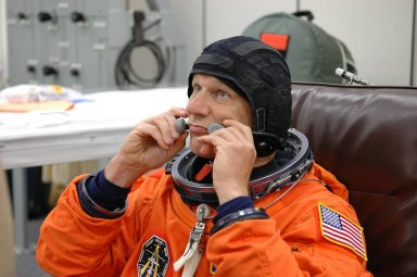 KENNEDY SPACE CENTER, FLA. - During suitup for launch today on Space Shuttle Discovery, STS-121 Mission Specialist Piers Sellers adjusts the communication device worn under his helmet. The launch is the 115th shuttle flight and the 18th U.S. flight to the International Space Station. During the 12-day mission, the STS-121 crew will test new equipment and procedures to improve shuttle safety, as well as deliver supplies and make repairs to the International Space Station. Photo credit: NASA/Kim Shiflett