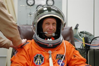 KENNEDY SPACE CENTER, FLA. - Prior to the third launch attempt on mission STS-121, Mission Specialist Thomas Reiter is helped with his helmet during suitup before heading to Launch Pad 39B. The July 2 launch attempt was scrubbed due to the presence of showers and thunderstorms within the surrounding area of the launch site. The launch of Space Shuttle Discovery on mission STS-121 is the 115th shuttle flight and the 18th U.S. flight to the International Space Station. During the 12-day mission, the STS-121 crew will test new equipment and procedures to improve shuttle safety, as well as deliver supplies and make repairs to the International Space Station. Photo credit: NASA/Kim Shiflett