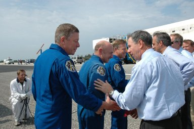 KENNEDY SPACE CENTER, FLA. - (From left) STS-121 Mission Specialist Michael Fossum, Pilot Mark Kelly and Commander Steven Lindsey are greeted by NASA Administrator Mike Griffin (foreground, right), Associate Administrator Rex Geveden and other senior managers after leaving the orbiter Discovery, in the background. The rest of the crew are Mission Specialists Piers Sellers, Lisa Nowak and Stephanie Wilson. Mission Specialist Thomas Reiter, who launched with the crew on July 4, remained on the station to join the Expedition 13 crew there. Discovery's smooth and perfect landing was on time at 9:14 a.m. EDT on Runway 15 of NASA's Shuttle Landing Facility after traveling 5.3 million miles on 202 orbits. Mission elapsed time was 12 days, 18 hours, 37 minutes and 54 seconds. The landing is the 62nd at Kennedy Space Center and the 32nd for Discovery. Photo credit: NASA/Kim Shiflett