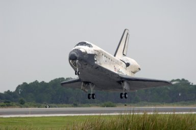 KENNEDY SPACE CENTER, FLA. - The orbiter Discovery drops toward Runway 15 at NASA's Shuttle Landing Facility for landing after completing mission STS-121 to the International Space Station. Discovery traveled 5.3 million miles, landing on orbit 202. Mission elapsed time was 12 days, 18 hours, 37 minutes and 54 seconds. Main gear touchdown occurred on time at 9:14:43 EDT. Wheel stop was at 9:15:49 EDT. The returning crew members aboard are Commander Steven Lindsey, Pilot Mark Kelly and Mission Specialists Piers Sellers, Michael Fossum, Lisa Nowak and Stephanie Wilson. Mission Specialist Thomas Reiter, who launched with the crew on July 4, remained on the station to join the Expedition 13 crew there. The landing is the 62nd at Kennedy Space Center and the 32nd for Discovery. Discovery's landing was as exhilarating as its launch, the first to take place on America's Independence Day. During the mission, the STS-121 crew tested new equipment and procedures to improve shuttle safety, and delivered supplies and made repairs to the International Space Station. Photo credit: NASA/Tim Powers