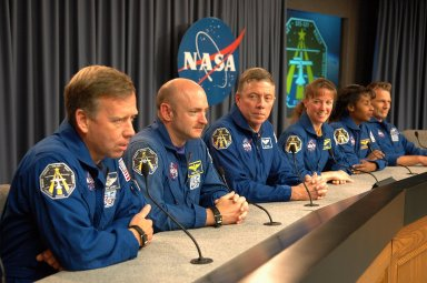 KENNEDY SPACE CENTER, FLA. - Several hours after their successful landing at Kennedy Space Center aboard the orbiter Discovery, the crew of mission STS-121 address questions from the media about their experiences on the shuttle and the International Space Station. Seated at the conference table are (from left) Commander Steven Lindsey, Pilot Mark Kelly and Mission Specialists Michael Fossum, Lisa Nowak, Stephanie Wilson and Piers Sellers. Discovery traveled 5.3 million miles, landing on orbit 202. Mission elapsed time was 12 days, 18 hours, 37 minutes and 54 seconds. During the nearly 13-day mission, the STS-121 crew tested new equipment and procedures to improve shuttle safety, and delivered supplies and made repairs to the International Space Station. Photo credit: NASA/Kim Shiflett