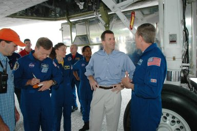 KENNEDY SPACE CENTER, FLA. - During the traditional post-flight walk-around after the landing of an orbiter, Mission Specialist Michael Fossum (right) talks with LeRoy Cain, manager of Shuttle Launch Integration. Other crew members seen are (from left) Commander Steven Lindsey and Mission Specialists Lisa Nowak and Stephanie Wilson. Discovery's smooth and perfect landing was on time at 9:14 a.m. EDT on Runway 15 of NASA's Shuttle Landing Facility after traveling 5.3 million miles on 202 orbits. Mission elapsed time was 12 days, 18 hours, 37 minutes and 54 seconds. The landing is the 62nd at Kennedy Space Center and the 32nd for Discovery. Photo credit: NASA/Kim Shiflett