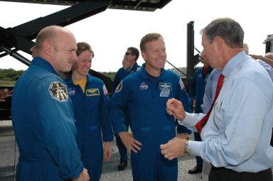 KENNEDY SPACE CENTER, FLA. - During the traditional post-flight walk-around after the landing of an orbiter, NASA Administrator Mike Griffin (right) shares a story with STS-121 Pilot Mark Kelly, Mission Specialist Lisa Nowak and Commander Steven Lindsey. Discovery's smooth and perfect landing was on time at 9:14 a.m. EDT on Runway 15 of NASA's Shuttle Landing Facility after traveling 5.3 million miles on 202 orbits. Mission elapsed time was 12 days, 18 hours, 37 minutes and 54 seconds. The landing is the 62nd at Kennedy Space Center and the 32nd for Discovery. Photo credit: NASA/Kim Shiflett