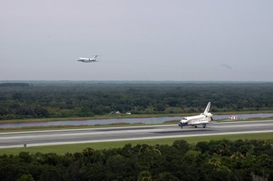 KENNEDY SPACE CENTER, FLA. - The orbiter Discovery makes a safe landing on Runway 15 at NASA's Shuttle Landing Facility, completing mission STS-121 to the International Space Station. Discovery traveled 5.3 million miles, landing on orbit 202. Mission elapsed time was 12 days, 18 hours, 37 minutes and 54 seconds. Main gear touchdown occurred on time at 9:14:43 EDT. Wheel stop was at 9:15:49 EDT. The returning crew members are Commander Steven Lindsey, Pilot Mark Kelly and Mission Specialists Piers Sellers, Michael Fossum, Lisa Nowak and Stephanie Wilson. Mission Specialist Thomas Reiter, who launched with the crew on July 4, remained on the station to join the Expedition 13 crew there. The landing is the 62nd at Kennedy Space Center and the 32nd for Discovery. Discovery's landing was as exhilarating as its launch, the first to take place on America's Independence Day. During the mission, the STS-121 crew tested new equipment and procedures to improve shuttle safety, and delivered supplies and made repairs to the International Space Station. Photo credit: NASA/Ken Thornsley