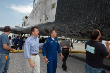 KENNEDY SPACE CENTER, FLA. - LeRoy Cain, manager of Shuttle Launch Integration, and Michael Fossum, STS-121 mission specialist, take a look at the orbiter Discovery during the traditional post-flight walk-around after the landing. Discovery's smooth and perfect landing was on time at 9:14 a.m. EDT on Runway 15 of NASA's Shuttle Landing Facility after traveling 5.3 million miles on 202 orbits. Mission elapsed time was 12 days, 18 hours, 37 minutes and 54 seconds. The landing is the 62nd at Kennedy Space Center and the 32nd for Discovery. Photo credit: NASA/Kim Shiflett