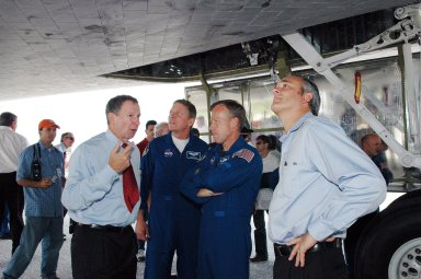 KENNEDY SPACE CENTER, FLA. - During the traditional post-flight walk-around after the landing of an orbiter, crew members Michael Fossum, mission specialist, and Steven Lindsey, commander, talk with NASA Administrator Mike Griffin (left). At right is Associate Administrator Rex Geveden. Discovery's smooth and perfect landing was on time at 9:14 a.m. EDT on Runway 15 of NASA's Shuttle Landing Facility after traveling 5.3 million miles on 202 orbits. Mission elapsed time was 12 days, 18 hours, 37 minutes and 54 seconds. The landing is the 62nd at Kennedy Space Center and the 32nd for Discovery. Photo credit: NASA/Kim Shiflett