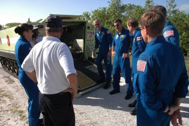 KENNEDY SPACE CENTER, FLA. - The STS-115 crew members are ready to climb into the M-113 armored personnel carrier with Capt. George Hoggard (back to camera), who is astronaut rescue team leader. The astronauts seen, left to right, are Mission Specialist Heidemarie Stefanyshyn-Piper, Commander Brent Jett, Mission Specialists Dan Burbank, Steven MacLean and Joe Tanner, and Pilot Christopher Ferguson. MacLean represents the Canadian Space Agency.The STS-115 crew are at NASA's Kennedy Space Center for Terminal Countdown Demonstration Test activities such as the M-113 training. They will also practice emergency egress from the launch pad and take part in a simulated launch countdown. Liftoff of mission STS-115 aboard Space Shuttle Atlantis is scheduled in a window beginning Aug. 27. Photo credit: NASA/Cory Huston