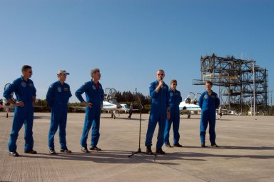 KENNEDY SPACE CENTER, FLA. - STS-115 Commander Brent Jett introduces his crew to waiting media at KSC's Shuttle Landing Facility after their arrival from Houston. At left are Mission Specialists Daniel Burbank, Steven MacLean and Joseph Tanner; at right are Mission Specialist Heidemarie Stefanyshyn-Piper and Pilot Christopher Ferguson. The STS-115 crew has flown to NASA's Kennedy Space Center to take part in Terminal Countdown Demonstration Test activities. The TCDT is a pre-launch preparation that includes practicing emergency egress from the pad, driving an M-113 armored personnel carrier, and simulating the launch countdown. Launch of STS-115 is currently scheduled for Aug. 27. Photo credit: NASA/George Shelton