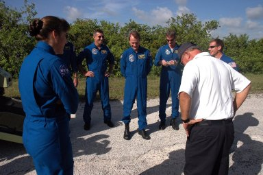 KENNEDY SPACE CENTER, FLA. - The STS-115 crew members talk about their upcoming driving practice on the M-113 armored personnel carrier with Capt. George Hoggard (back to camera), who is astronaut rescue team leader. The astronauts seen, left to right, are Mission Specialists Heidemarie Stefanyshyn-Piper, Dan Burbank, Steven MacLean and Joe Tanner, and Pilot Christopher Ferguson. Not visible is Commander Brent Jett. MacLean represents the Canadian Space Agency. The STS-115 crew are at NASA's Kennedy Space Center for Terminal Countdown Demonstration Test activities such as the M-113 training. They will also practice emergency egress from the launch pad and take part in a simulated launch countdown. Liftoff of mission STS-115 aboard Space Shuttle Atlantis is scheduled in a window beginning Aug. 27. Photo credit: NASA/Cory Huston