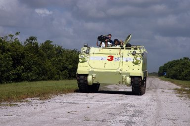 KENNEDY SPACE CENTER, FLA. - With a video camera trained on him, STS-115 Mission Specialist Daniel Burbank takes his turn driving the M-113 armored personnel carrier. Also along for the ride are Mission Specialist Daniel Burbank, Capt. George Hoggard, who is astronaut rescue team leader, and Mission Specialist Steven MacLean, who represents the Canadian Space Agency. The STS-115 crew are at NASA's Kennedy Space Center for Terminal Countdown Demonstration Test activities such as the M-113 training. They will also practice emergency egress from the launch pad and take part in a simulated launch countdown. Liftoff of mission STS-115 aboard Space Shuttle Atlantis is scheduled in a window beginning Aug. 27. Photo credit: NASA/Cory Huston