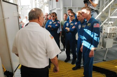 KENNEDY SPACE CENTER, FLA. - The STS-115 crew gets instructions about using the slidewire baskets for emergency egress from the space shuttle on the pad. Seen here are Mission Specialists Heidemarie Stefanyshyn-Piper and Daniel Burbank, Pilot Chris Ferguson, Mission Specialist Steven MacLean and Commander Brent Jett. MacLean is with the Canadian Space Agency. Not seen is Mission Specialist Joseph Tanner. The mission crew is at KSC for Terminal Countdown Demonstration Test (TCDT) activities that are preparation for launch on Space Shuttle Atlantis, scheduled to take place in a window that opens Aug. 27. During their 11-day mission to the International Space Station, the STS-115 crew will continue construction of the station and attach the payload elements, the Port 3/4 truss segment with its two large solar arrays. Photo credit: NASA/Cory Huston