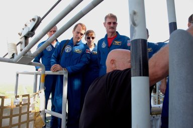 KENNEDY SPACE CENTER, FLA. - The STS-115 crew gets instructions about using the slidewire baskets for emergency egress from the space shuttle on the pad. From left are Commander Brent Jett and Mission Specialists Steven MacLean, Heidemarie Stefanyshyn-Piper and Joseph Tanner. MacLean is with the Canadian Space Agency. Not pictured are Pilot Chris Ferguson and Mission Specialist Daniel Burbank. The mission crew is at KSC for Terminal Countdown Demonstration Test (TCDT) activities that are preparation for launch on Space Shuttle Atlantis, scheduled to take place in a window that opens Aug. 27. During their 11-day mission to the International Space Station, the STS-115 crew will continue construction of the station and attach the payload elements, the Port 3/4 truss segment with its two large solar arrays. Photo credit: NASA/Cory Huston