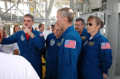 KENNEDY SPACE CENTER, FLA. - The STS-115 crew gets instructions about using the slidewire baskets for emergency egress from the space shuttle on the pad. At center, foreground, is Commander Brent Jett. The others, from left are Mission Specialists Joseph Tanner, gesturing, Steven MacLean, Daniel Burbank and Heidemarie Stefanyshyn-Piper. MacLean is with the Canadian Space Agency. The mission crew is at KSC for Terminal Countdown Demonstration Test (TCDT) activities that are preparation for launch on Space Shuttle Atlantis, scheduled to take place in a window that opens Aug. 27. During their 11-day mission to the International Space Station, the STS-115 crew will continue construction of the station and attach the payload elements, the Port 3/4 truss segment with its two large solar arrays. Photo credit: NASA/Cory Huston