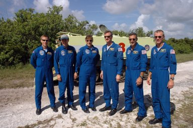 KENNEDY SPACE CENTER, FLA. - After successfully completing their driving practice on the M-113 armored personnel carrier behind them, the STS-115 crew poses for a photo. From left are Pilot Christopher Ferguson, Mission Specialists Steven MacLean, Heidemarie Stefanyshyn-Piper, Joseph Tanner and Daniel Burbank, and Commander Brent Jett. The STS-115 crew are at NASA's Kennedy Space Center for Terminal Countdown Demonstration Test activities such as the M-113 training. They will also practice emergency egress from the launch pad and take part in a simulated launch countdown. Liftoff of mission STS-115 aboard Space Shuttle Atlantis is scheduled in a window beginning Aug. 27. Photo credit: NASA/Cory Huston