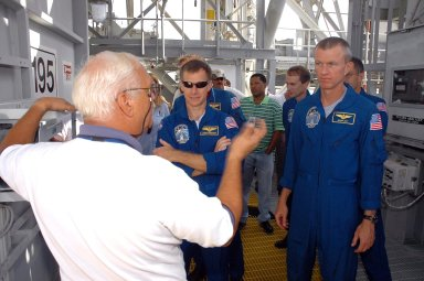 KENNEDY SPACE CENTER, FLA. - The STS-115 crew gets instructions about using the slidewire baskets for emergency egress from the space shuttle on the pad. In the front, at left, is Pilot Chris Ferguson; at right is Commander Brent Jett. The other crew members are Mission Specialists Heidemarie Stefanyshyn-Piper, Joseph Tanner and Daniel Burbank. MacLean is with the Canadian Space Agency. The mission crew is at KSC for Terminal Countdown Demonstration Test (TCDT) activities that are preparation for launch on Space Shuttle Atlantis, scheduled to take place in a window that opens Aug. 27. During their 11-day mission to the International Space Station, the STS-115 crew will continue construction of the station and attach the payload elements, the Port 3/4 truss segment with its two large solar arrays. Photo credit: NASA/Cory Huston