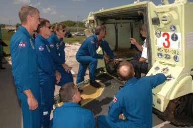 KENNEDY SPACE CENTER, FLA. - STS-115 crew members take another look at an M-113 armored personnel carrier that could be used to move quickly away from the launch pad in the event of an emergency. From left are Commander Brent Jett, Pilot Chris Ferguson and Mission Specialists Heidemarie Stefanyshyn-Piper and Joseph Tanner. In the foreground are Mission Specialists Daniel Burbank and Steven MacLean, who is with the Canadian Space Agency. The mission crew is at KSC for Terminal Countdown Demonstration Test (TCDT) activities that are preparation for launch on Space Shuttle Atlantis, scheduled to take place in a window that opens Aug. 27. During their 11-day mission to the International Space Station, the STS-115 crew will continue construction of the station and attach the payload elements, the Port 3/4 truss segment with its two large solar arrays. Photo credit: NASA/Cory Huston
