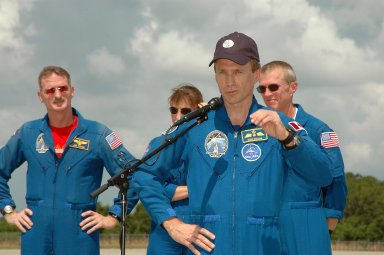 KENNEDY SPACE CENTER, FLA. - The crew of mission STS-115 stop to talk to the media after arriving at NASA Kennedy Space Center's Shuttle Landing Facility to prepare for launch on Aug. 27 to the International Space Station. Seen here, left to right, are Mission Specialists Joseph Tanner, Heidemarie Stefanyshyn-Piper and Steven MacLean (at the microphone), and Commander Brent Jett. The mission will deliver and install the 17-and-a-half-ton P3/P4 truss segment to the port side of the integrated truss system on the orbital outpost. The truss includes a new set of photovoltaic solar arrays. When unfurled to their full length of 240 feet, the arrays will provide additional power for the station in preparation for the delivery of international science modules over the next two years. STS-115 is expected to last 11 days and includes three scheduled spacewalks. Photo credit: NASA/Kim Shiflett