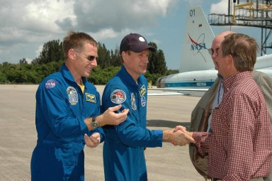KENNEDY SPACE CENTER, FLA. - The crew of mission STS-115 arrives at NASA Kennedy Space Center's Shuttle Landing Facility to prepare for launch on Aug. 27 to the International Space Station. Seen here are (left to right) Pilot Christopher Ferguson and Mission Specialist Steven MacLean being greeted by KSC Associate Director Jim Hattaway and Shuttle Launch Director Mike Leinbach. The mission will deliver and install the 17-and-a-half-ton P3/P4 truss segment to the port side of the integrated truss system on the orbital outpost. The truss includes a new set of photovoltaic solar arrays. When unfurled to their full length of 240 feet, the arrays will provide additional power for the station in preparation for the delivery of international science modules over the next two years. STS-115 is expected to last 11 days and includes three scheduled spacewalks. Photo credit: NASA/Kim Shiflett