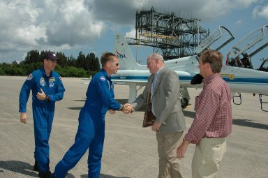 KENNEDY SPACE CENTER, FLA. - The crew of mission STS-115 arrives at NASA Kennedy Space Center's Shuttle Landing Facility to prepare for launch on Aug. 27 to the International Space Station. Seen here are (left to right) Mission Specialist Steven MacLean and Pilot Christopher Ferguson being greeted by KSC Associate Director Jim Hattaway and Shuttle Launch Director Mike Leinbach. The mission will deliver and install the 17-and-a-half-ton P3/P4 truss segment to the port side of the integrated truss system on the orbital outpost. The truss includes a new set of photovoltaic solar arrays. When unfurled to their full length of 240 feet, the arrays will provide additional power for the station in preparation for the delivery of international science modules over the next two years. STS-115 is expected to last 11 days and includes three scheduled spacewalks. Photo credit: NASA/Kim Shiflett