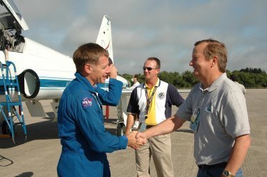 KENNEDY SPACE CENTER, FLA. - The crew of mission STS-115 arrives at NASA Kennedy Space Center's Shuttle Landing Facility to prepare for a second launch attempt on Sept. 6 to the International Space Station. Seen here is Pilot Christopher Ferguson (left) shaking hands with Shuttle Launch Director Mike Leinbach. Mission managers cancelled Atlantis' first launch campaign due to a lightning strike at the pad and the passage of Tropical Storm Ernesto along Florida's east coast. The mission will deliver and install the 17-and-a-half-ton P3/P4 truss segment to the port side of the integrated truss system on the orbital outpost. The truss includes a new set of photovoltaic solar arrays. When unfurled to their full length of 240 feet, the arrays will provide additional power for the station in preparation for the delivery of international science modules over the next two years. STS-115 is expected to last 11 days and includes three scheduled spacewalks. Photo credit: NASA/Kim Shiflett