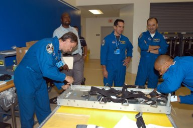 KENNEDY SPACE CENTER, FLA. - Members of the STS-116 crew examine components of the mission payload at SPACEHAB in Cape Canaveral, Fla. From left are Mission Specialist Christer Fuglesang , Pilot William Oefelein, Commander Mark Polansky and Mission Specialist Robert Curbeam. Fuglesang, who represents the European Space Agency, and Curbeam practice techniques for removing and replacing the rack front stowage tray, used inside the SPACEHAB module. Mission crews make frequent trips to the Space Coast to become familiar with the equipment and payloads they will be using. STS-116 will be mission number 20 to the International Space Station and construction flight 12A.1. The mission payload is the SPACEHAB module, the P5 integrated truss structure and other key components. Launch is scheduled for no earlier than Dec. 7. Photo credit: NASA/George Shelton