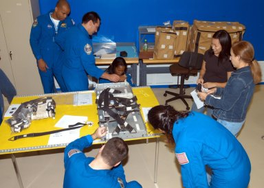 KENNEDY SPACE CENTER, FLA. - Members of the STS-116 crew examine components of the mission payload at SPACEHAB in Cape Canaveral, Fla. In the background are Mission Specialist Robert Curbeam, Pilot William Oefelein and Mission Specialist Joan Higginbotham. In the foreground are Mission Specialist Nicholas Patrick and Sunita Williams. The Swedish Fuglesang represents the European Space Agency. On the table is a rack front stowage tray used inside the SPACEHAB module. Mission crews make frequent trips to the Space Coast to become familiar with the equipment and payloads they will be using. STS-116 will be mission number 20 to the International Space Station and construction flight 12A.1. The mission payload is the SPACEHAB module, the P5 integrated truss structure and other key components. Launch is scheduled for no earlier than Dec. 7. Photo credit: NASA/George Shelton